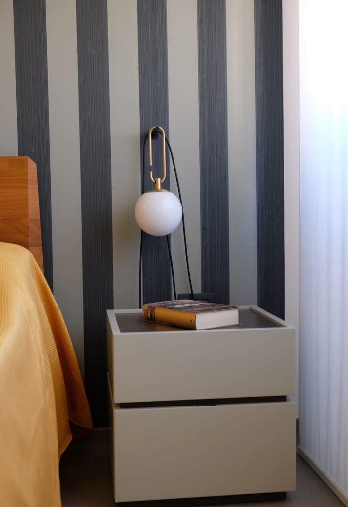 camera da letto carta da parati e lampada design comodino due cassetti