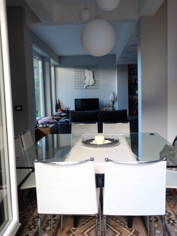 zona pranzo tavolo cristallo sedie design lampadario design vista dal giardino