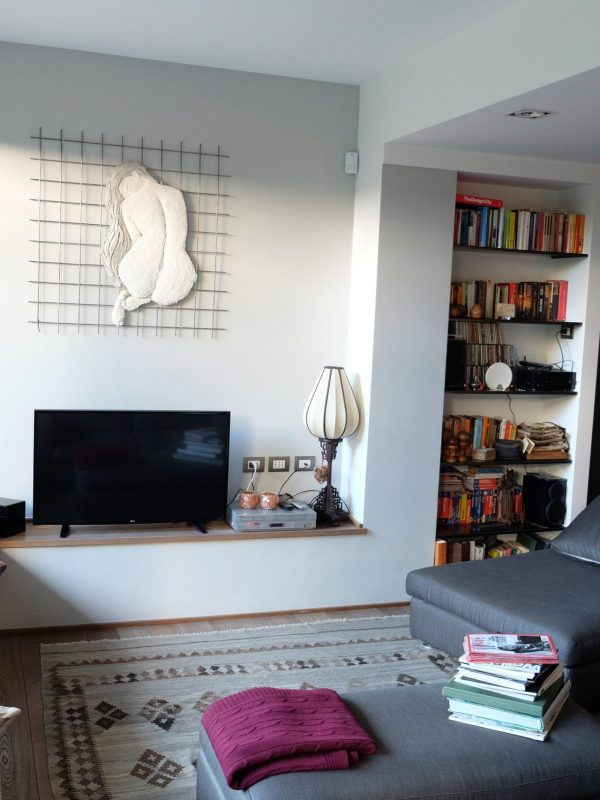 salone zona tv e conversazione divani tessuto grigio scuro tappeto lilim opera d'arte contemporanea