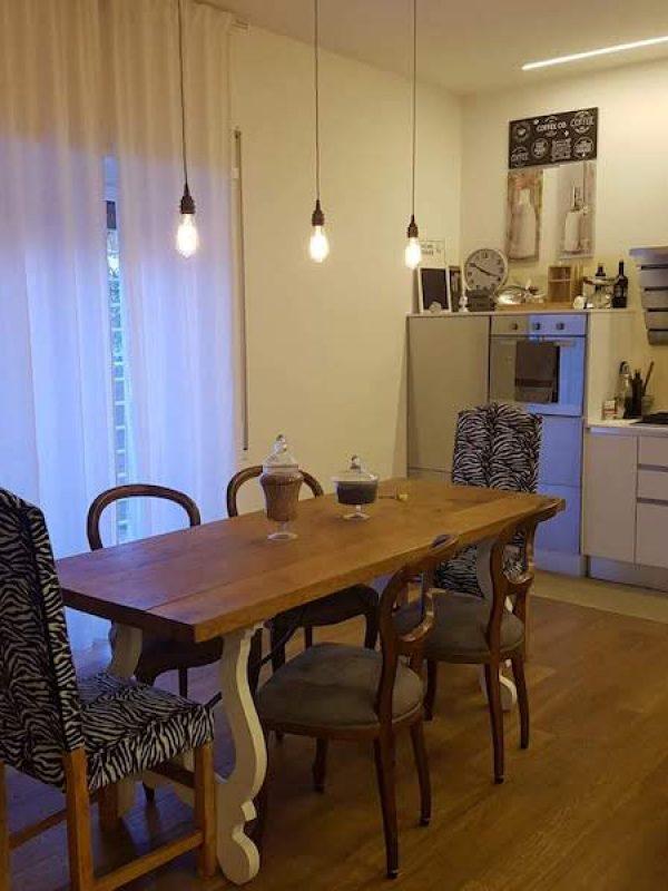 architetto Roma ristrutturazione vista zona pranzo cucina open space tavolo sabbi sedie vintage parquet rovere