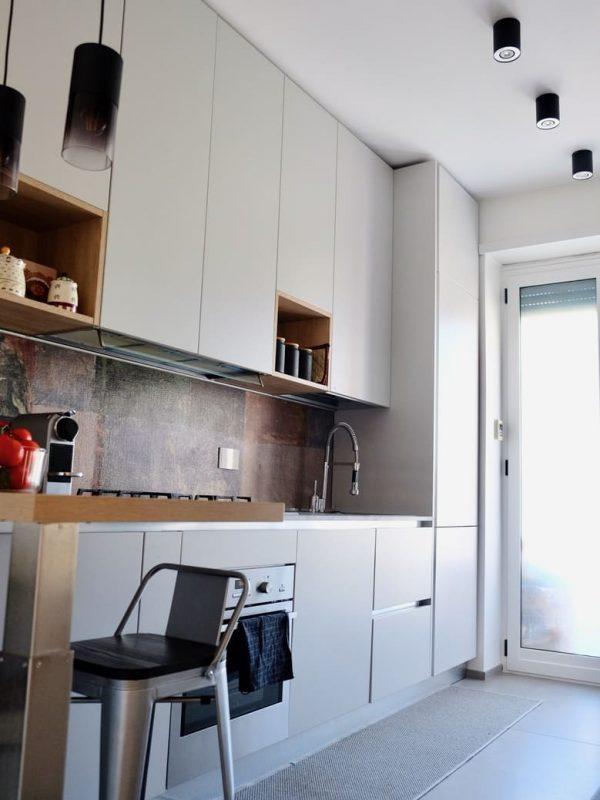 parete cucina con vista snack in legno e zampa in acciaio satinato