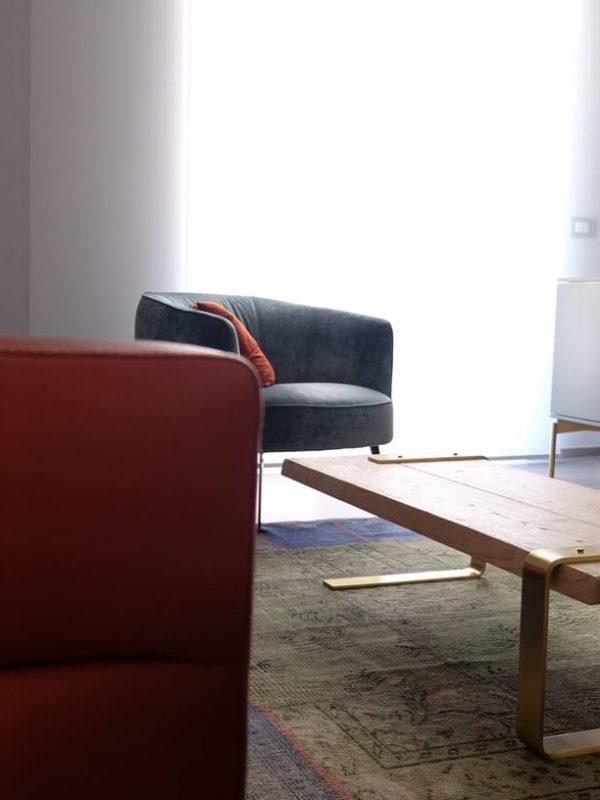 vista salotto divano pelle color mattone poltrona stile retrò in velluto tavolino caffè disegno e realizzazione su misura stile industrial-chic